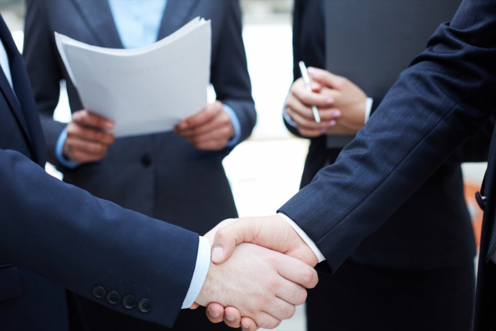 Business men shaking hands while businessman in background holds papers. Visit Us at our Miami location for the Best filing services. Need Florida filing, document filing, court filing, legal filing. All filing solutions here. Florida Filing Best Filing Services